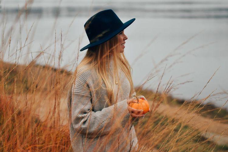Woman wearing hat standing at lake