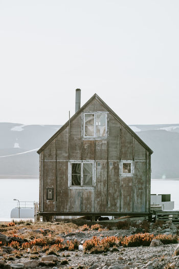 House on field by sea against clear sky