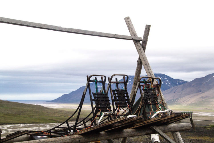 Dog sleds stored during the summer in Longyearbyen, Svalbard in the Arctic Mountain Sky Environment Beauty In Nature Nature Day Cloud - Sky Landscape Mountain Range Scenics - Nature No People Tranquil Scene Tranquility Outdoors Transportation Non-urban Scene Wood - Material Land Remote Dog Sleds Longyearbyen Svalbard  Spitsbergen Dogs Arctic