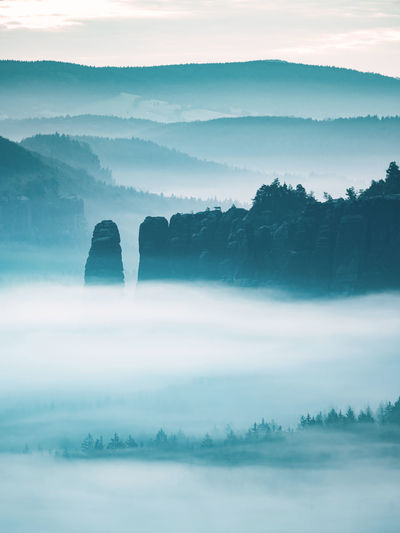 Mountain peak outline in blue night mist. row of foggy mountain ranges in sachsen deutschland park.
