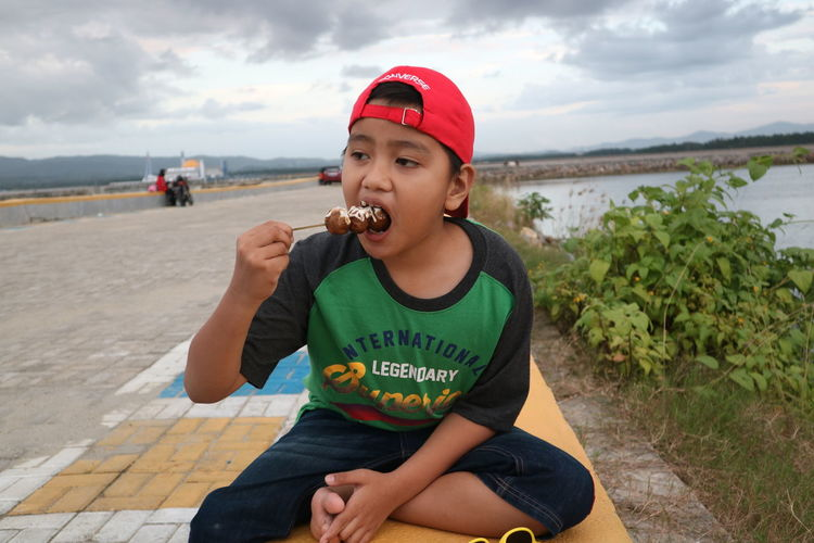 Boy eating food while sitting against sky
