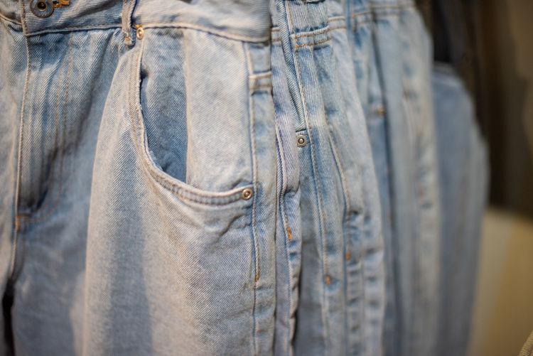 Denim jeans hanging on shelf at retail store