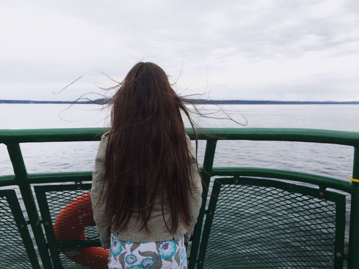 Rear view of woman with long hair traveling in boat over lake against sky