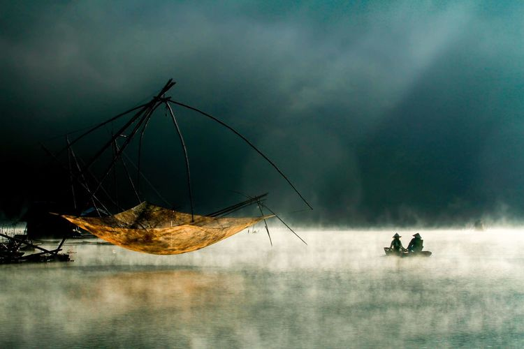 People in boat on lake by fishing net during foggy weather