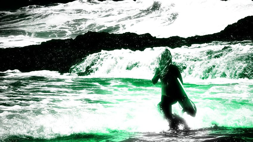Female surfer wades into surf that appears luminous around her. Filter effect. Leisure Activity Lifestyles Luminous Motion Night Light Show Phosphorescence In The Sea. Surf Surfboard Surfing Water Wave The Colour Of Sport