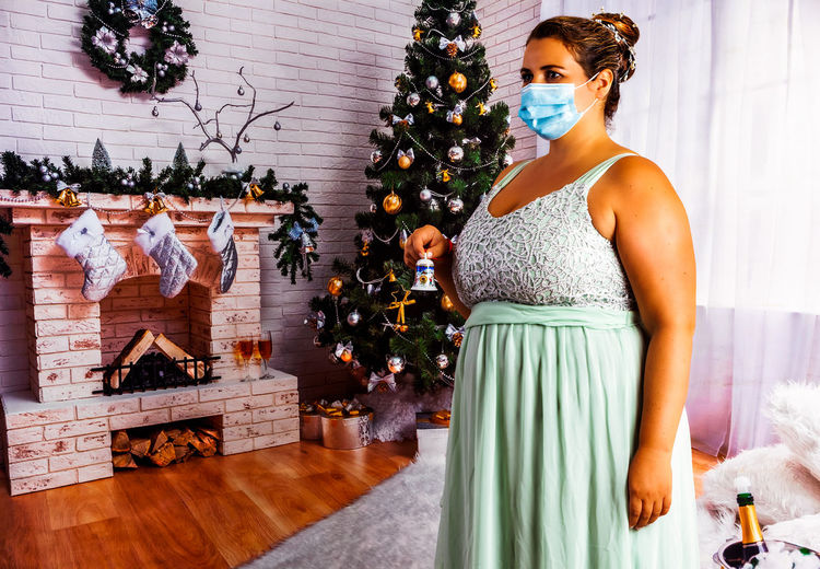 Midsection of woman with christmas tree at home