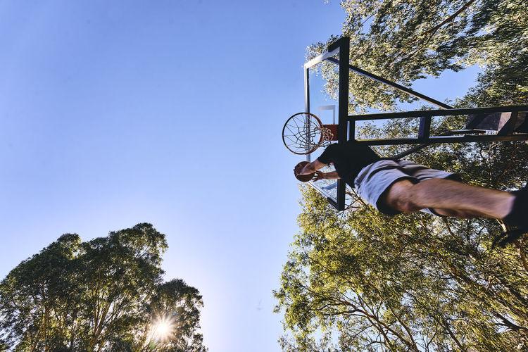 Tilt Shot Of Man Playing Basketball On Court At Park