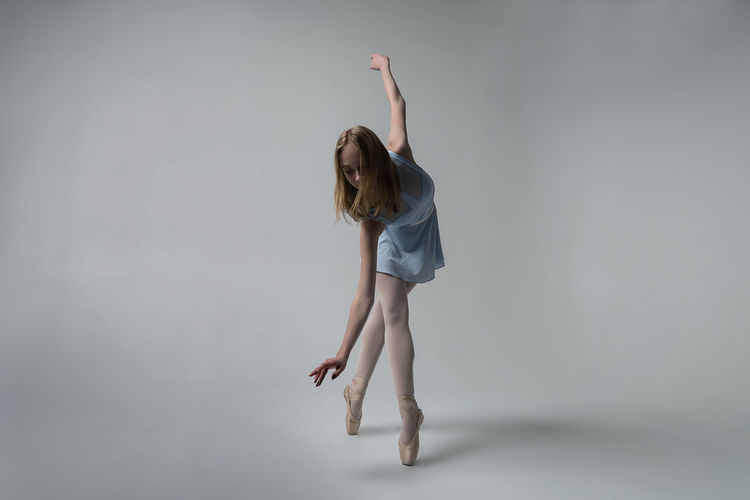 Ballet dancing against gray background