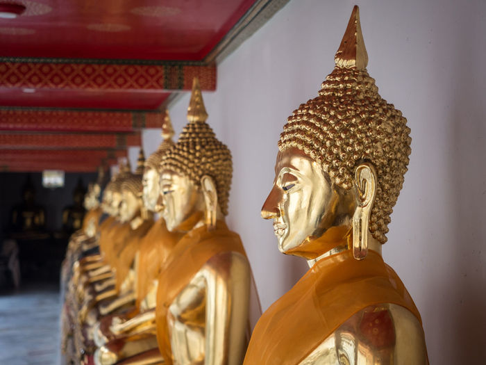 Row of golden buddha statues at wat pho temple, bangkok, thailand