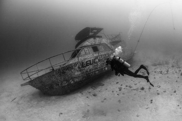 Scuba diver exploring sunken ship underwater