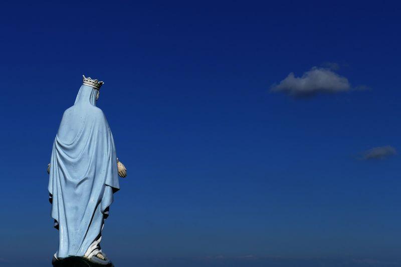 Statue of virgin marry against blue sky