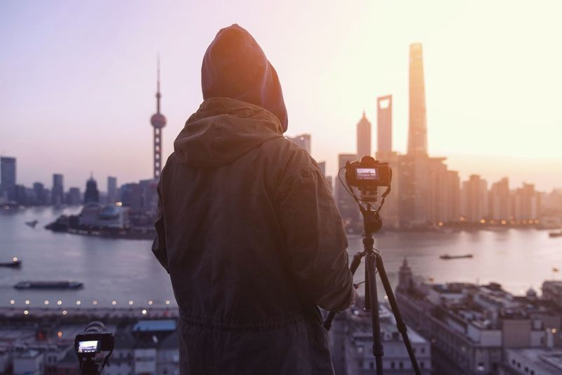 Rear View Of Person With Tripod Standing Against Cityscape During Sunset