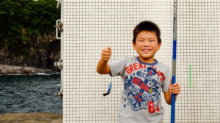 Portrait of smiling boy holding fishing rod