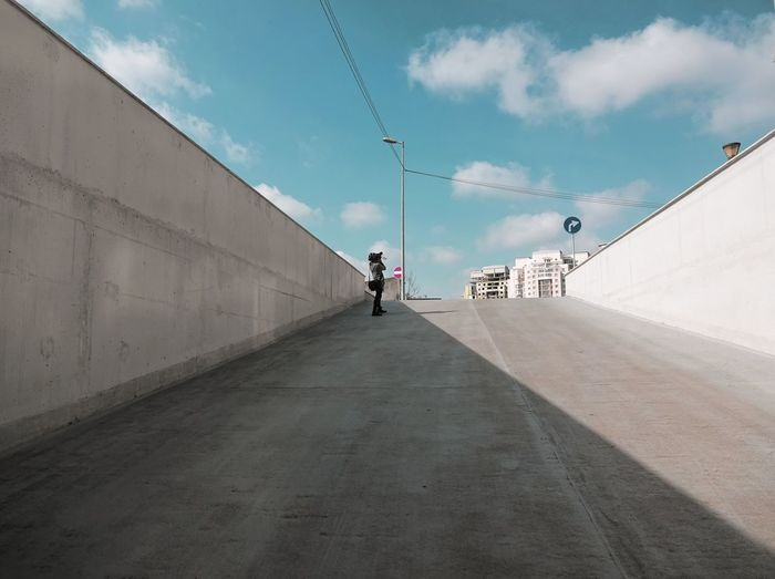 Person Standing On Road Against Cloudy Sky