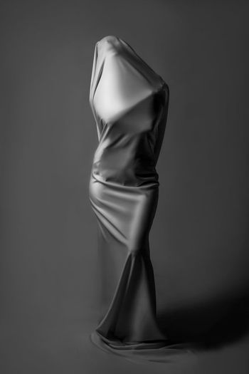 Mannequin wrapped in textile against gray background