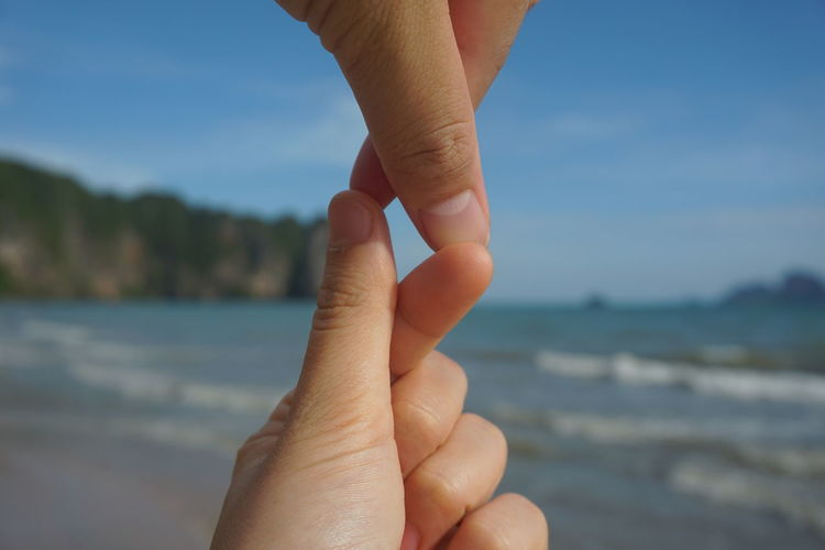 Cropped couple joining fingers at beach