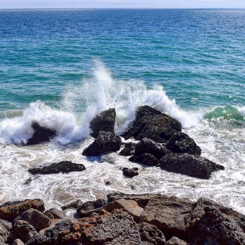 Sea Water Surf Beach Rock - Object Wave Beauty In Nature Majestic Scenics Shore Nature Travel Destinations Tranquil Scene Splashing Tranquility Day Rocky Power In Nature Rock Tourism