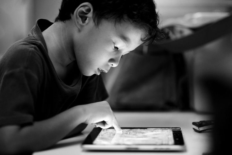 Side View Of Boy Using Digital Tablet