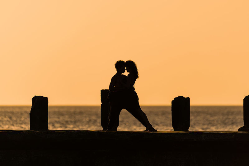 Silhouette dancers on sea against sky during sunset