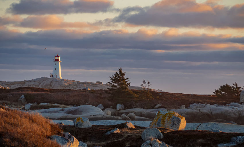 Lighthouse on rock against sky during sunset