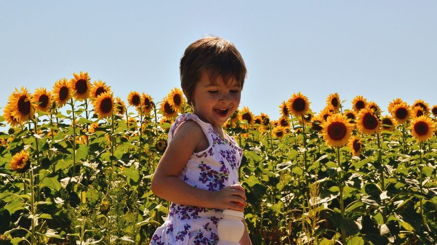 Girl Standing By Flowers Against Clear Sky
