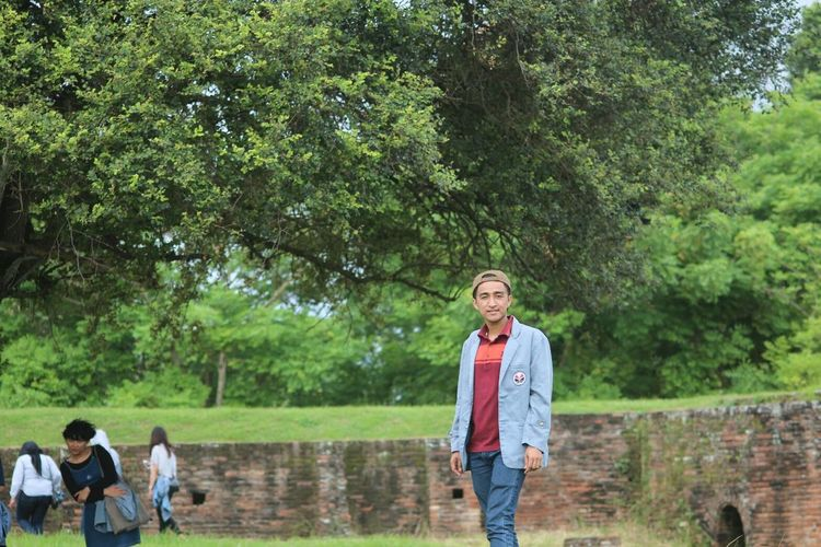 Young Man Standing Against Trees At Park With Friends In Background
