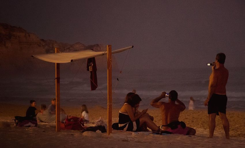People at beach against sky during twilight