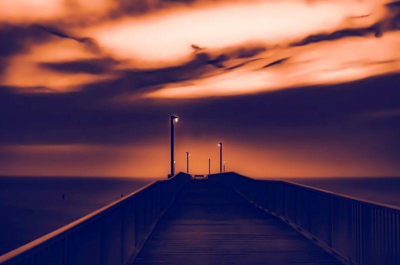 In the Glow Fiery Pier Lights Bench Foggy Day Bridge - Man Made Structure Fog Water Sea Sunset Beach Horizon Harbor Lighthouse Jetty Water's Edge Pier Romantic Sky Seascape Coastal Feature Atmospheric Mood Coastline Tide Moody Sky Calm Dramatic Sky