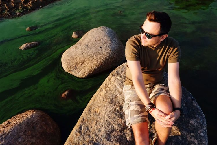 Saint-Petersburg, 30.09.2018. A man is sitting on a rock near the water. Last Days Of Summer Stones & Water Stone Water Sunset Glasses Leisure Activity Lifestyles Nature Men Young Men Outdoors Sitting Sunglasses Day Front View