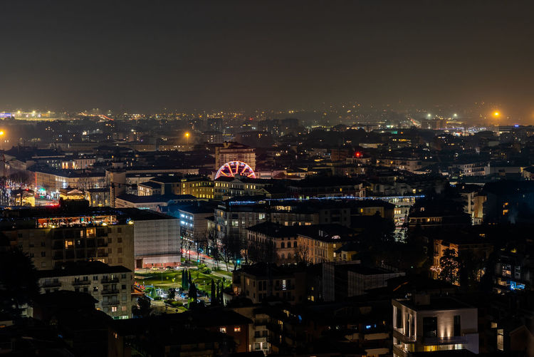 Night view of bergamo seen from città alta, detail of ferris wheel installed for the christmas time