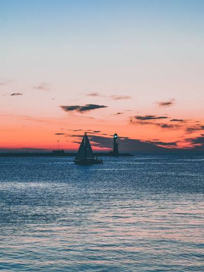 Silhouette boat sailing in sea against sky during sunset