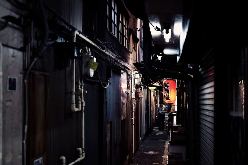 Illuminated alley amidst buildings