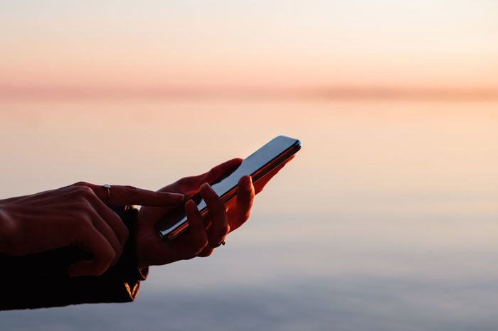Hands holding smart phone against sky during sunset