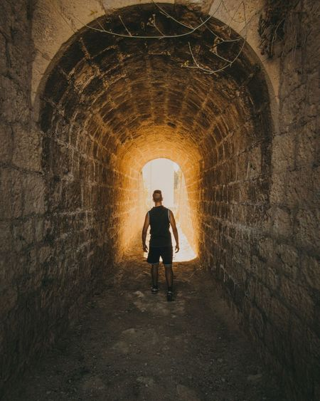 Full length rear view of man standing in tunnel