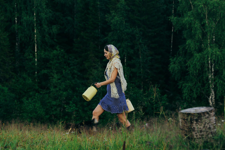 Rustic young woman in blue polka dot dress with cans