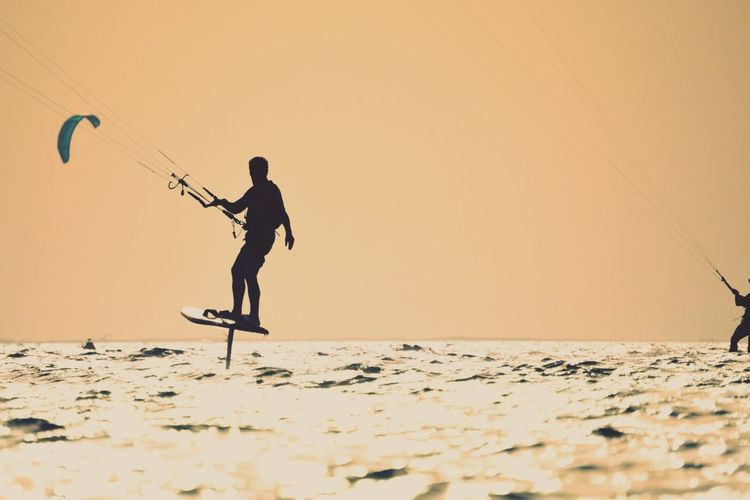 Silhouette of person kiteboarding