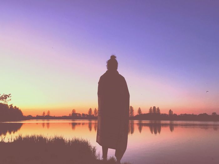 Rear view of silhouette woman standing by lake against sky during sunset
