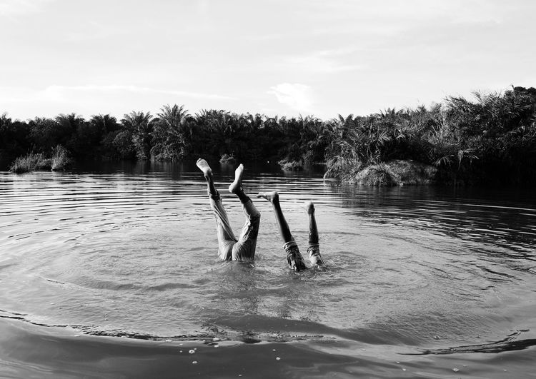 People swimming in lake against sky