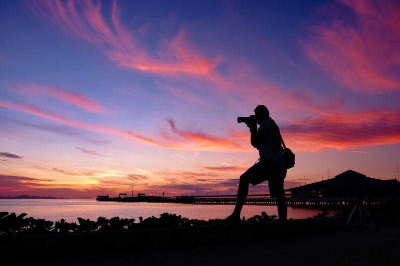 Silhouette Man Photographing Sea During Sunset
