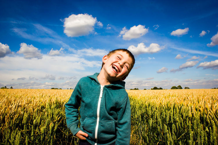 Cheerful Boy Standing On Field Against Sky