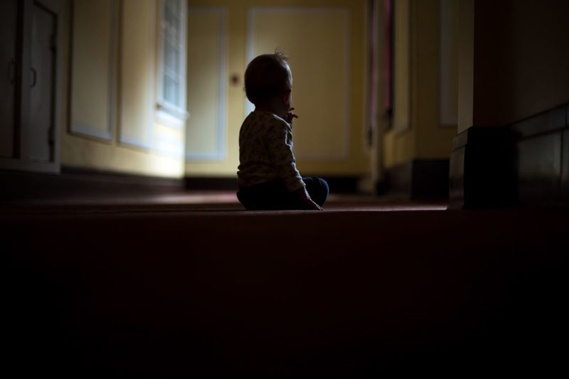 Rear view of child sitting on floor at home