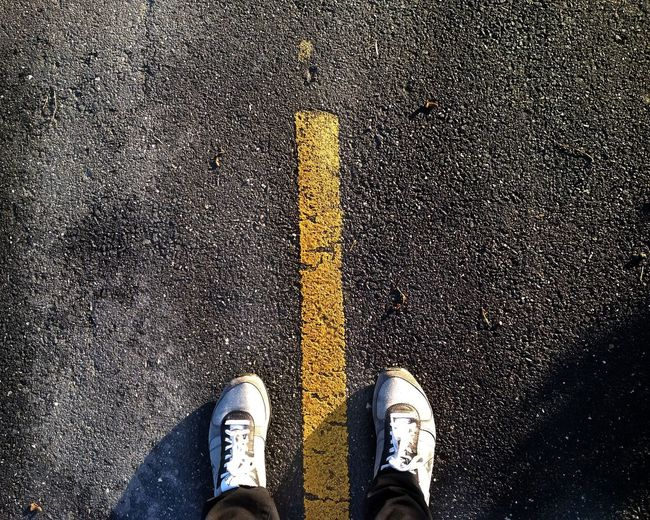 Low section of man standing on road marking