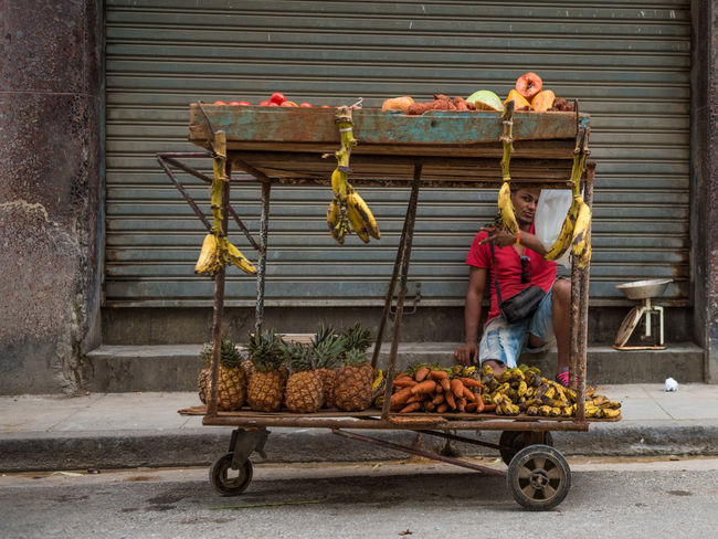 """Havana Fruit stall. During my stay, I haven't seen any supermarkets in Havana. I have seen plenty street vendors. Some advertised their presence by shouting and some used a whistle to let the whole street know they're there. Others just parked their home-made cart near a corner and opened up shop. (Nikon D810 24.0-70.0 mm f/2.8 ƒ/3.2 44mm 1/400"""" iso 200) Adult Adults Only Caribbean Colorful Day Editorial  Food Freshness Fruit Fruit Stall Healthy Eating Man One Person Outdoors People Real People Selling Streetphotography The Street Photographer - 2017 EyeEm Awards Travel Working Young Adult Food Stories An Eye For Travel"""