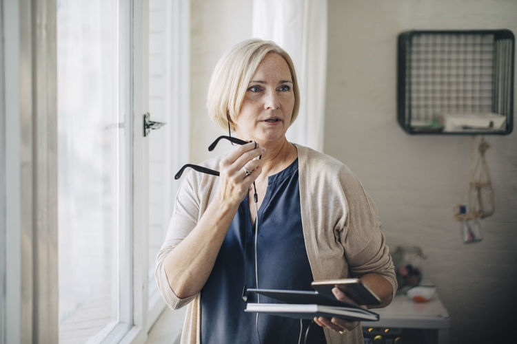 Mature businesswoman talking through earphones while standing by window in office