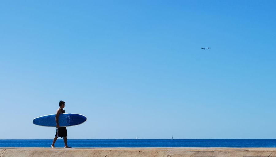 Woman flying over beach against clear blue sky