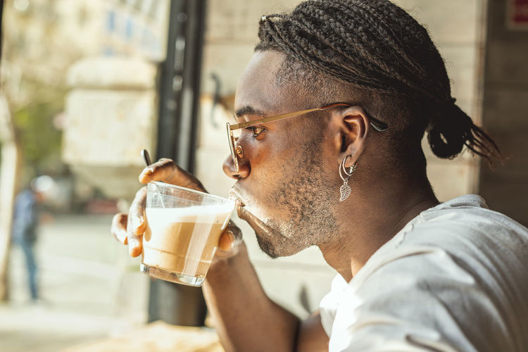 Portrait of young man drinking glass