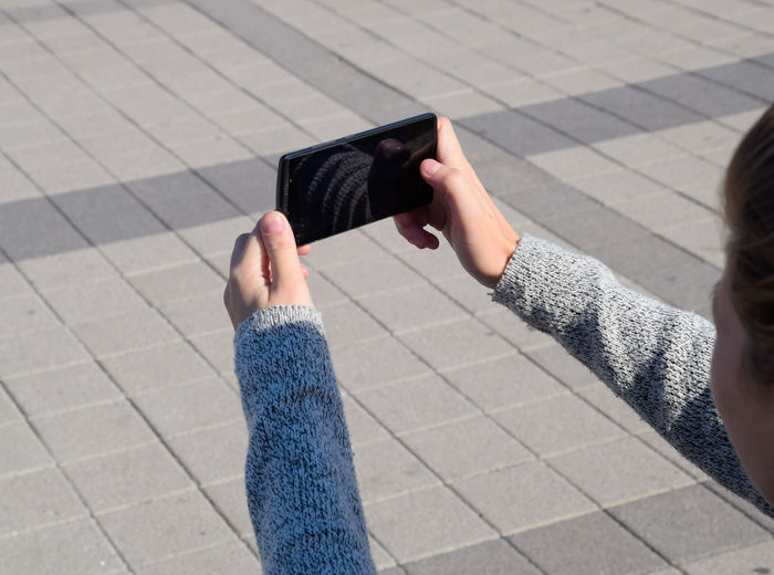 Cropped image of woman using mobile phone outdoors