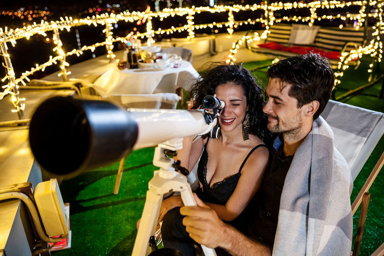 Smiling Man Standing By Woman Looking Through Telescope On Illuminated Terrace At Night