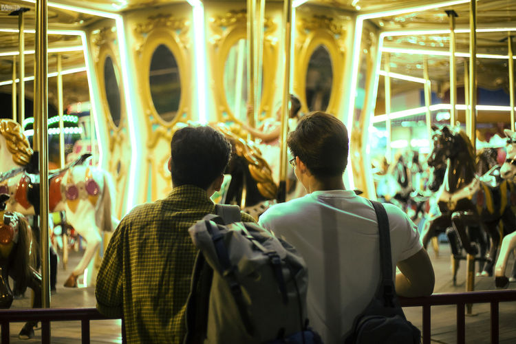 Rear view of people walking in amusement park at night