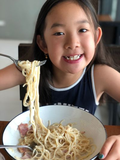 Portrait of girl having noodles